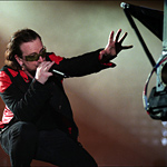 Bono crouches on the stage and 3D-enhanced animation follows Bono's hand gestures