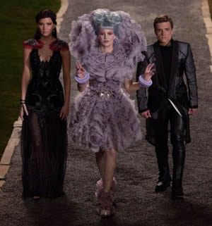Goodbye Yellow Brick Road? Hunger Champions flank Effie Trinket